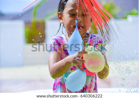 child playing  water balloons.