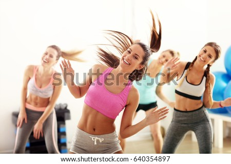 Group of happy people with coach dancing in gym