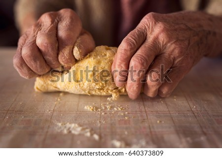 Detail of an elderly woman's hand kneading dough while making homemade pasta. Selective focus #640373809