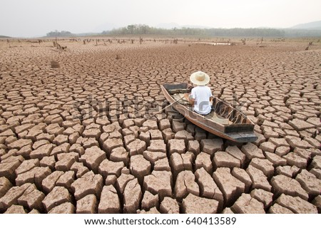Climate change, The man on wood boat at large drought land Royalty-Free Stock Photo #640413589