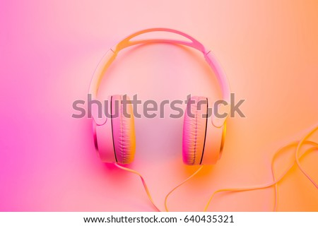 Headphones on colorful (multicolor tonal transitions) background. Poster layout with free text (copy) space.  Royalty-Free Stock Photo #640435321