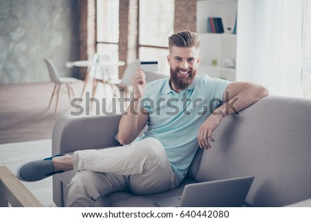 Online shopping concept. Portrait of handsome young man sitting on sofa at home with laptop and showing credit card #640442080