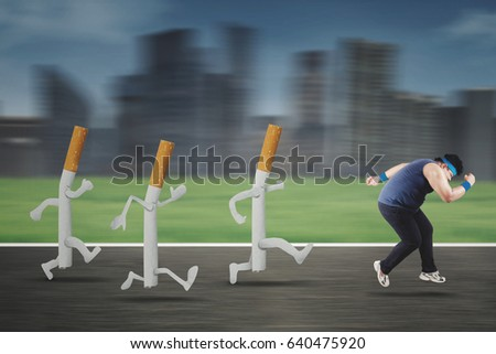 Picture of an obese man escaping by three cigarettes while running on the road