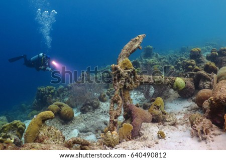 Scuba diver and anchor underwater in tropical sea. Scuba diving reef underwater scenery. Remains of old ship underwater with scuba diver explorer. Adventure scuba diving on the reef with ship wreck. #640490812