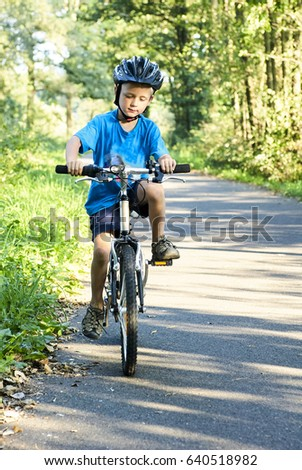 Child boy on a bicycle in the bicycle path. Boy cycling outdoors in safety helmet #640518982