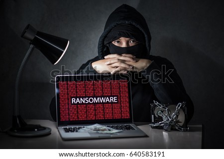 Hacker with computer screen showing ransomware attacking, alert in red digital binary background with hard disk drive lock. Cyber attack concept