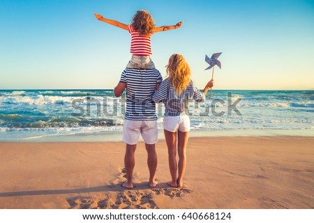 Happy family on the beach. People having fun on summer vacation. Father, mother and child against blue sea and sky background. Holiday travel concept #640668124
