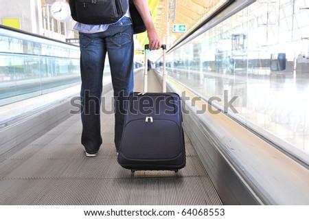 Traveler with a bag at the speedwalk #64068553