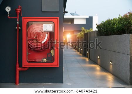 Fire extinguisher and fire hose reel in hotel corridor #640743421
