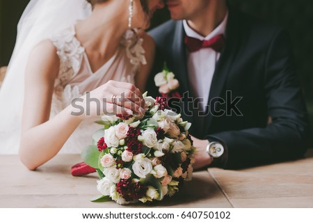 bride and groom in a cafe. wedding bouquet on a wooden table in a restaurant bride and groom hold each other's hands. Wedding rings. Loving couple in a cafe. hot tea for lovers Royalty-Free Stock Photo #640750102
