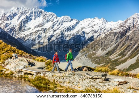 New zealand travel hikers hiking in Mt Cook trail to Mueller Hut. Tramping lifestyle couple tourists walking on alpine route in alps with snow capped mountains in background. #640768150