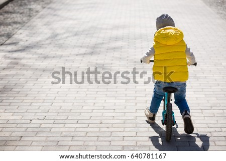 Back view on cute toddler boy riding his bike. Child on bicycle in the park. #640781167