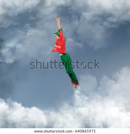 A boy dressed in Peter's Pan costume flying in a sky.