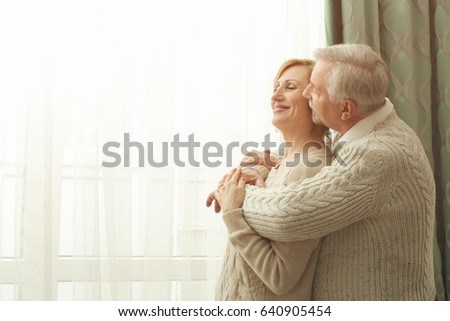 Cute elderly couple near window at home #640905454