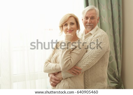 Cute elderly couple near window at home #640905460