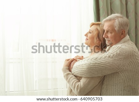 Cute elderly couple near window at home #640905703