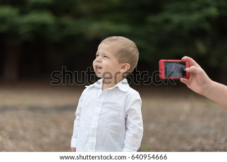 Young boy in white shirt getting his photo taken by a red iphone #640954666