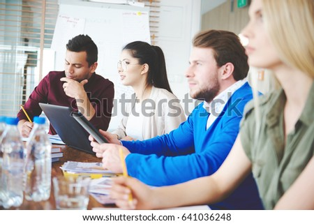 Side view of young coworkers listening to presentation #641036248