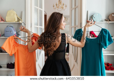 Image of young lady standing in clothes shop indoors choosing dresses. Looking aside. Royalty-Free Stock Photo #641053810
