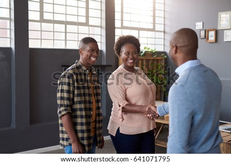 Two casually dressed young African business colleagues standing in a large modern office smiling and shaking hands together while another coworker looks on #641071795