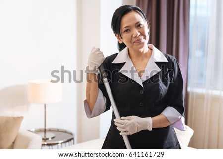 Delighted positive chambermaid looking at you #641161729
