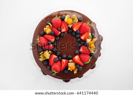 Cake in chocolate with strawberries, blueberries and physalis. Top view. Picture for a menu or a confectionery catalog.