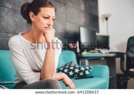 Sad woman sitting on a sofa in the living room Royalty-Free Stock Photo #641208637