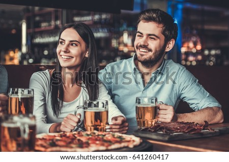 Handsome friends smile and talk while relaxing in pub with beer, snacks and pizza. #641260417