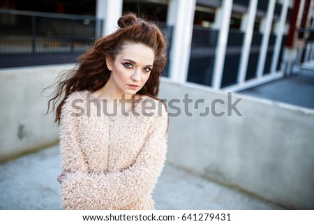 Beautiful young woman with long brown hair posing at the  outdoors #641279431