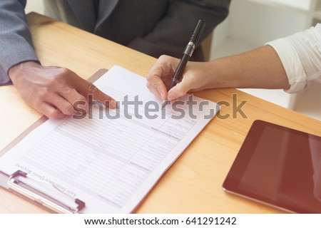 Person's hand hold ballpoint pen writing on blank application form paper sheet, fill in empty document template, applying for auto car insurance #641291242