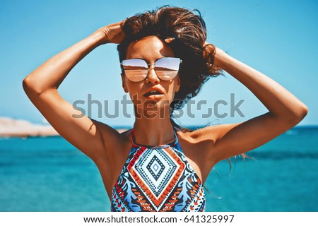 Outdoor fashion photo of beautiful happy woman at sea. Beach travel. Summer vibes