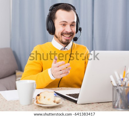 Young male student studying at online courses productively at home #641383417