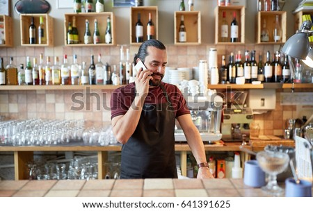 small business, communication, people and service concept - happy man or waiter in apron calling on smartphone at bar or coffee shop #641391625