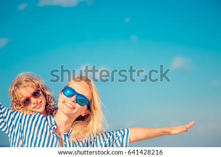 Happy family on the beach. People having fun on summer vacation. Mother and child against blue sea and sky background. Holiday travel concept #641428216