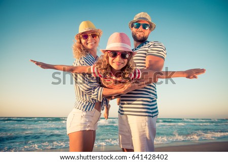 Happy family on the beach. People having fun on summer vacation. Father, mother and child against blue sea and sky background. Holiday travel concept #641428402