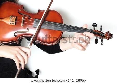 Violin player hands. Violinist playing violin close up Royalty-Free Stock Photo #641428957