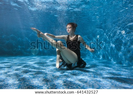 Dancing woman under the water in the pool. Surrealistic photography. #641432527