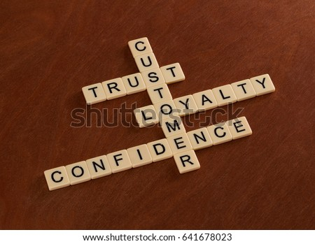 Crossword puzzle with words Trust, Loyalty, Confidence. Customer loyalty concept. Ivory tiles with capital letters on mahogany board. #641678023