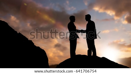 Digital composite of Silhouette businessmen shaking hands during sunset #641706754