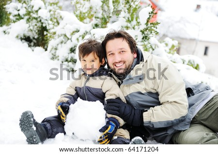 Young father and little boy playing together with snow and making snowman #64171204