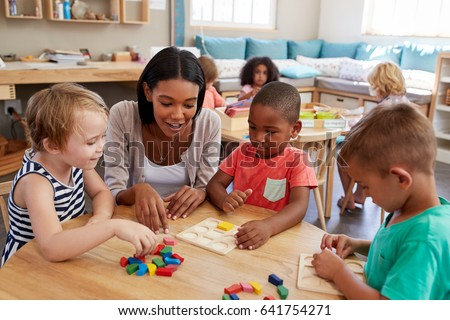 Teacher And Pupils Using Wooden Shapes In Montessori School #641754271