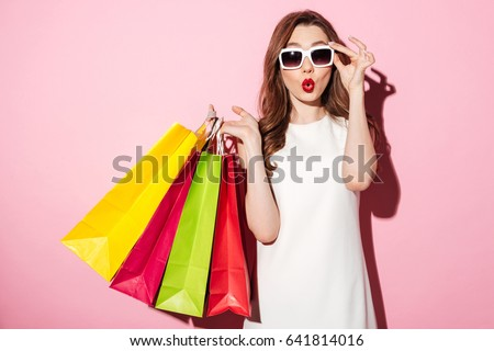 Picture of a shocked young brunette woman in white summer dress wearing sunglasses posing with shopping bags and looking at camera over pink background. #641814016