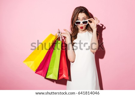 Image of a shocked young brunette lady in white summer dress wearing sunglasses posing with shopping bags and looking at camera over pink background. #641814046