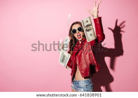 Portrait of a young happy woman winner throwing money banknotes isolated over pink