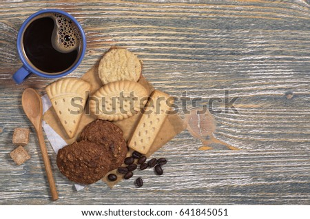 Blue cup of hot coffee and different shortbread cookies on old wooden table, top view #641845051
