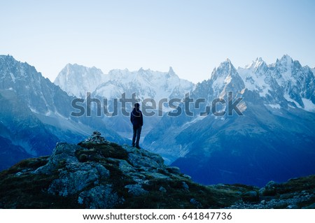 Man looking at the mountains near Chamonix, France. Old film style. #641847736