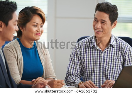 Cheerful mature Asian businessman discussing his idea with investors #641861782