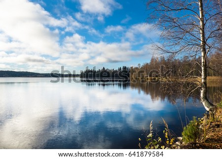 Scenic landscape with lake reflection at bright spring day in Finland