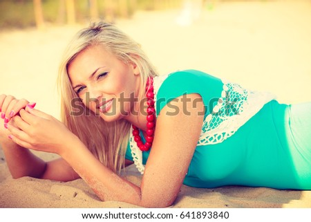 Portrait of attractive blonde woman lying on sandy beach relaxing during summertime #641893840