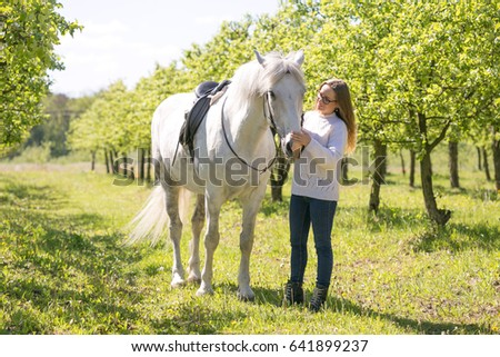 Beautiful girl is driving a white horse. #641899237